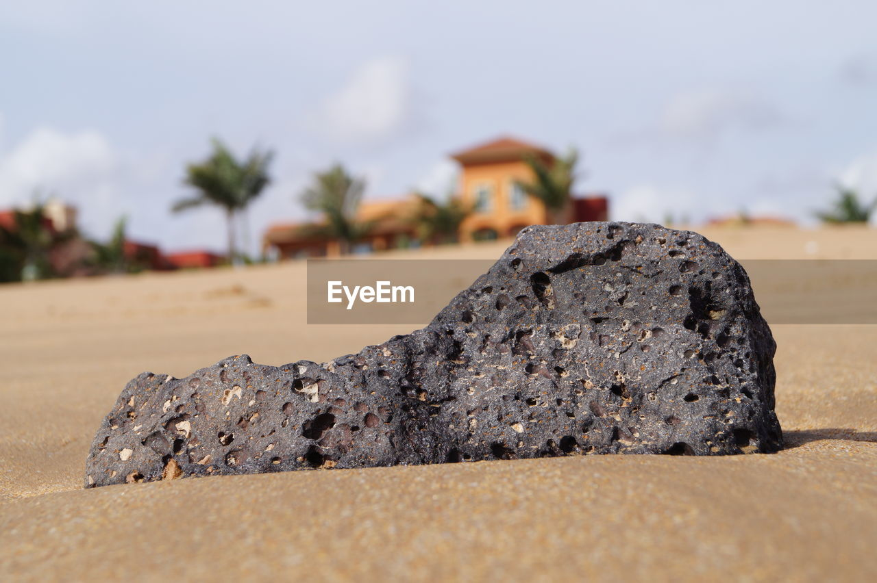 Close-Up Of Rock On Sand Against Sky