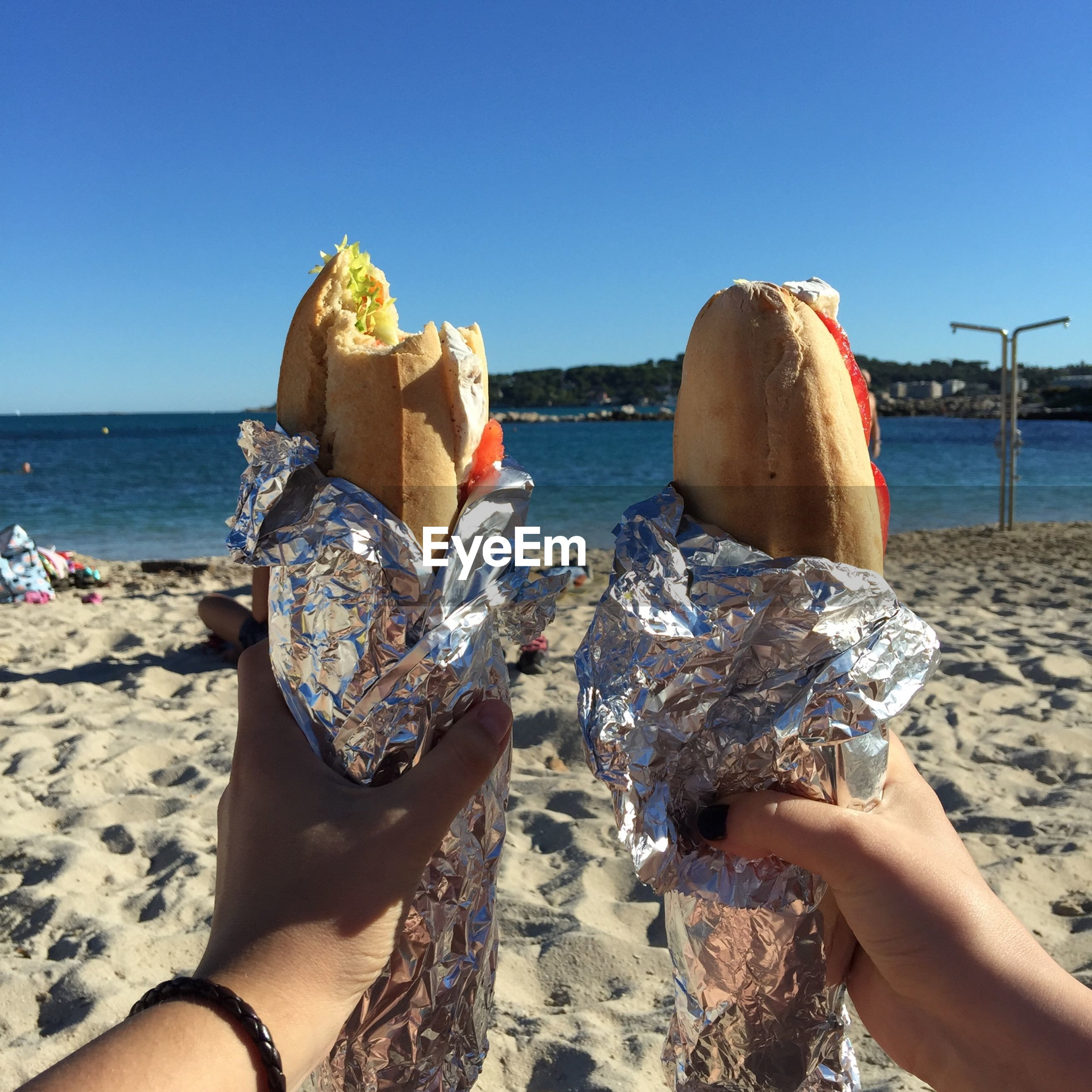 Cropped hands holding sandwiches on beach