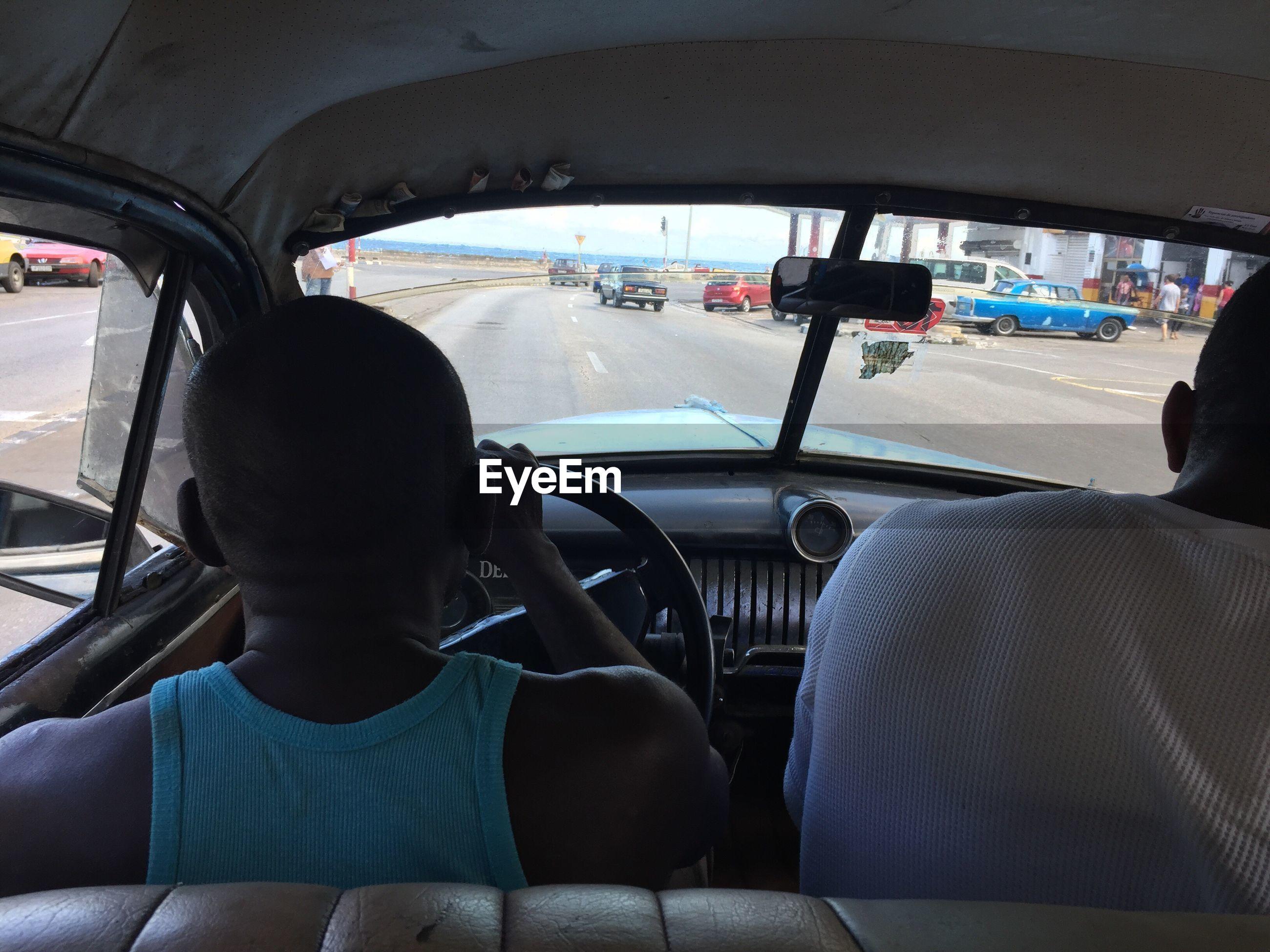 REAR VIEW OF SENIOR MAN SITTING IN CAR