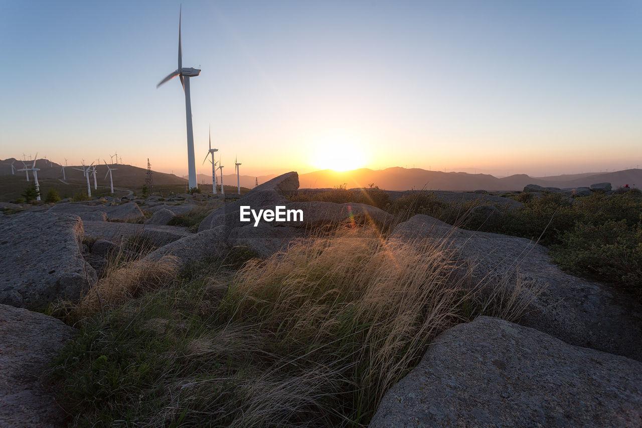 WIND TURBINES ON LANDSCAPE AGAINST SUNSET SKY