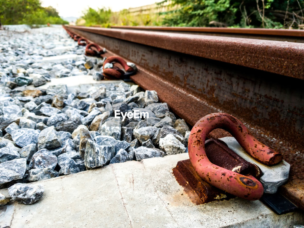 CLOSE-UP OF RUSTY METAL CHAIN ON RAILROAD TRACK