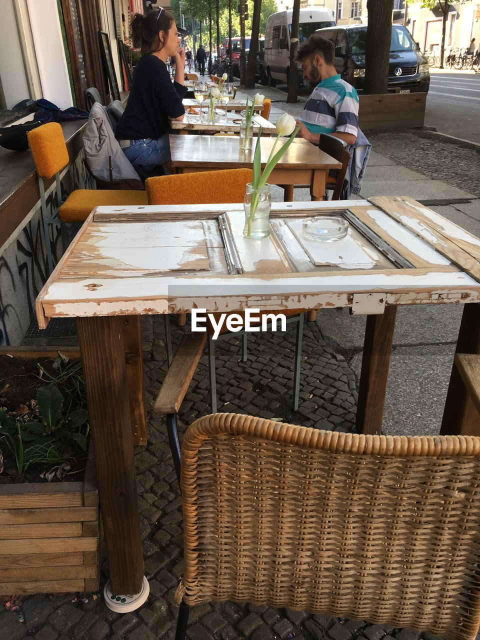table, seat, sitting, real people, chair, food and drink, business, leisure activity, lifestyles, restaurant, drink, two people, cafe, casual clothing, wood - material, men, incidental people, day, refreshment, young adult, glass