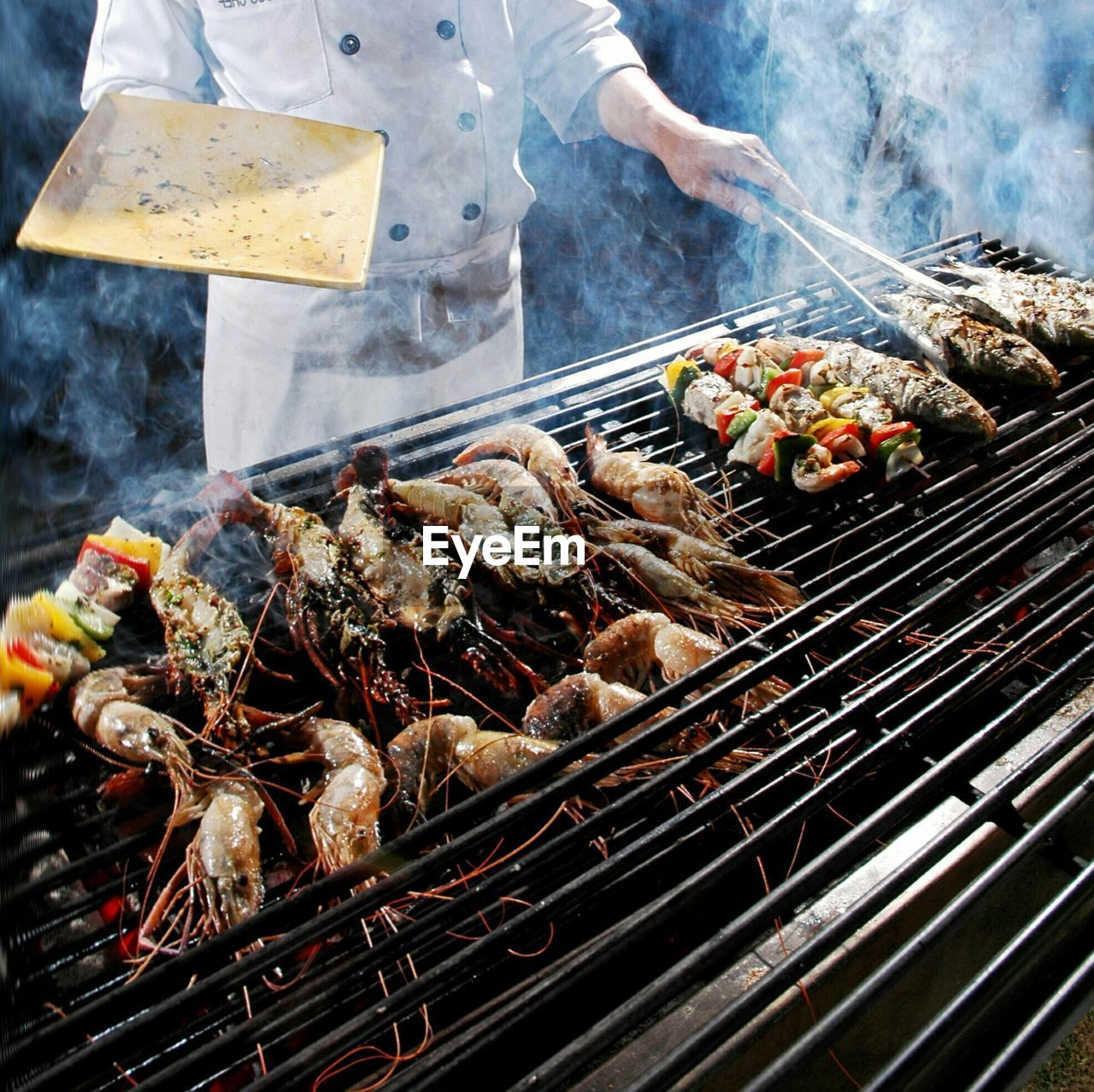 barbecue grill, grilled, barbecue, food and drink, smoke - physical structure, preparation, food, heat - temperature, coal, freshness, seafood, preparing food, outdoors, one person, healthy eating, skewer, meat, serving tongs, squid, day, kebab, midsection, human body part, prawn, men, real people, cooked, char-grilled, close-up, one man only, human hand, people, adult, ready-to-eat