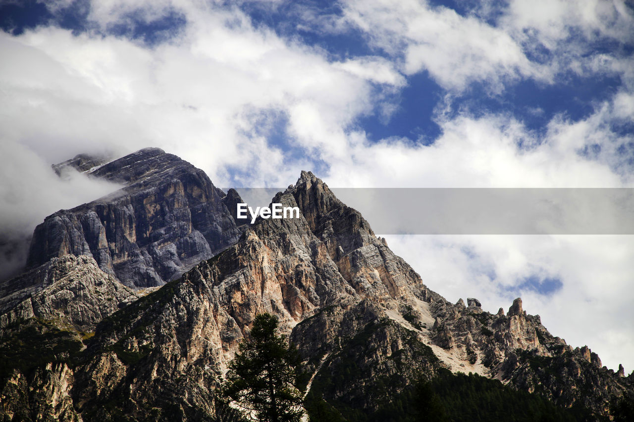 Low Angle View Of Dolomites Against Cloudy Sky