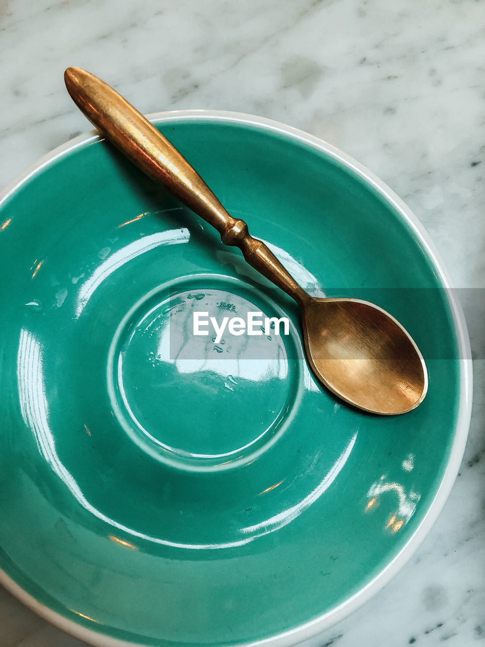 spoon, still life, high angle view, table, close-up, no people, eating utensil, kitchen utensil, bowl, green color, indoors, metal, glasses, fashion, focus on foreground, household equipment, plate, food and drink, sunglasses, steel, crockery, turquoise colored