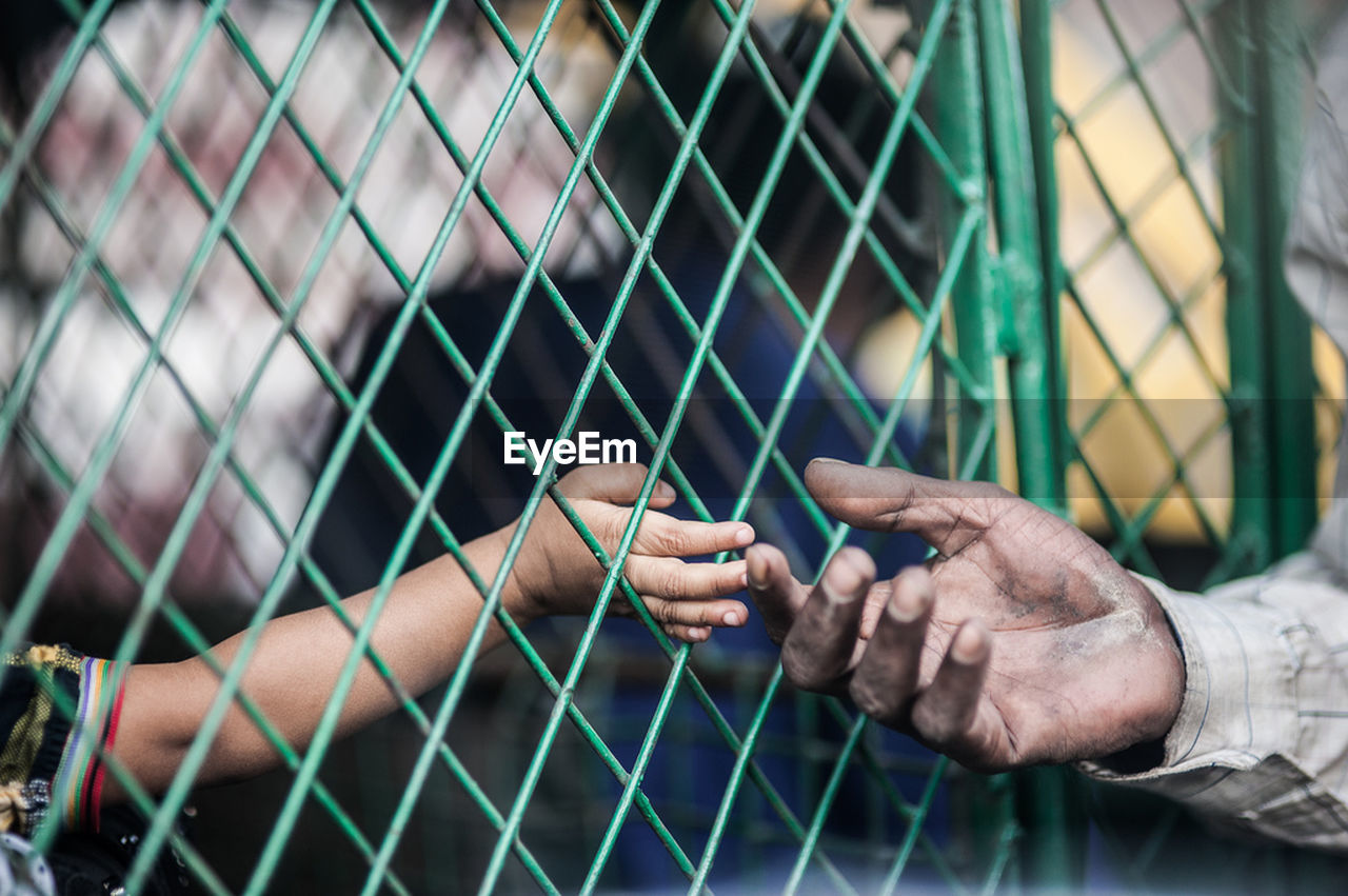 Close-up of girl hand reaching to father through fence