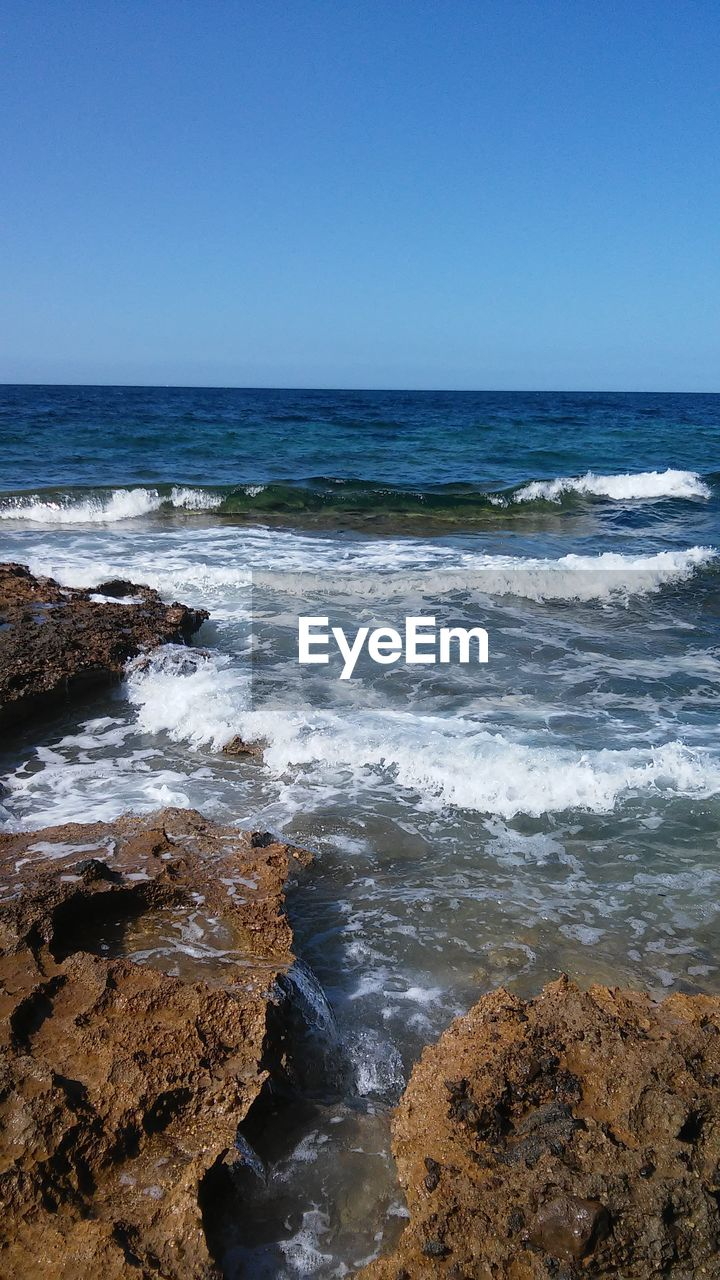 sea, water, nature, horizon over water, beauty in nature, scenics, clear sky, tranquil scene, no people, rock - object, wave, tranquility, outdoors, day, beach, sky, sunlight, blue