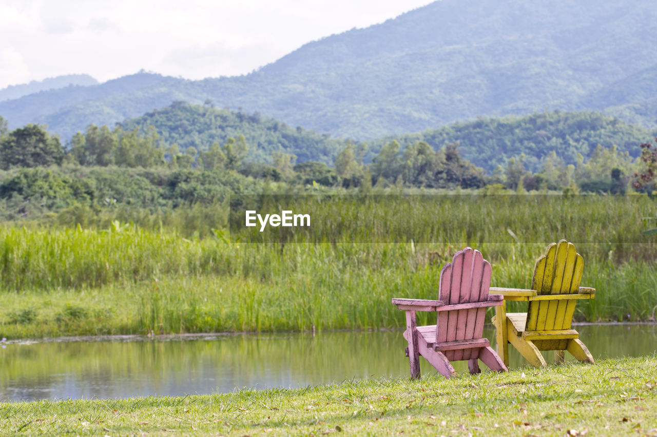 CHAIR ON GRASSY FIELD BY LAKE