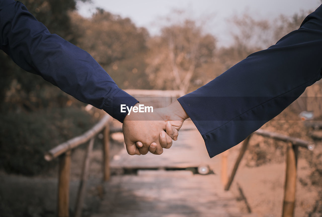 Cropped image of couple holding hands outdoors
