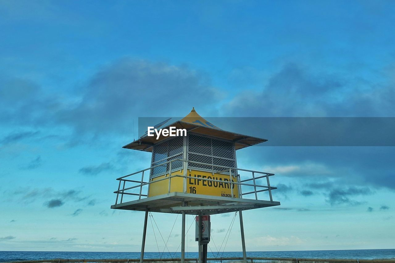 sea, water, cloud - sky, sky, safety, horizon over water, lifeguard hut, built structure, tranquility, outdoors, lifeguard, tranquil scene, architecture, beach, nature, day, yellow, lookout tower, no people, beauty in nature, scenics