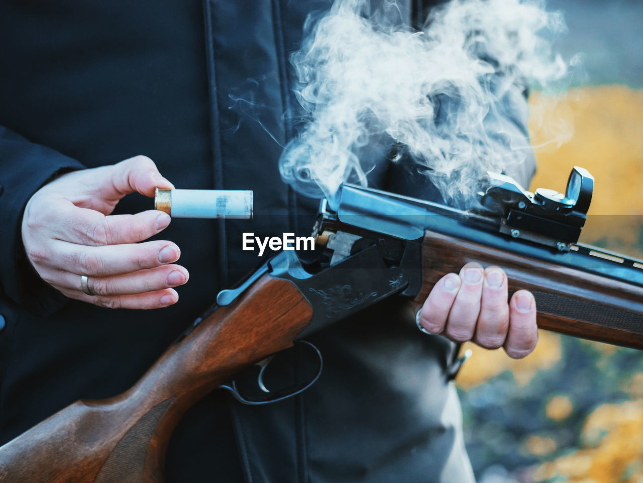 Midsection Of Man Removing Bullet From Shotgun While Standing Outdoors