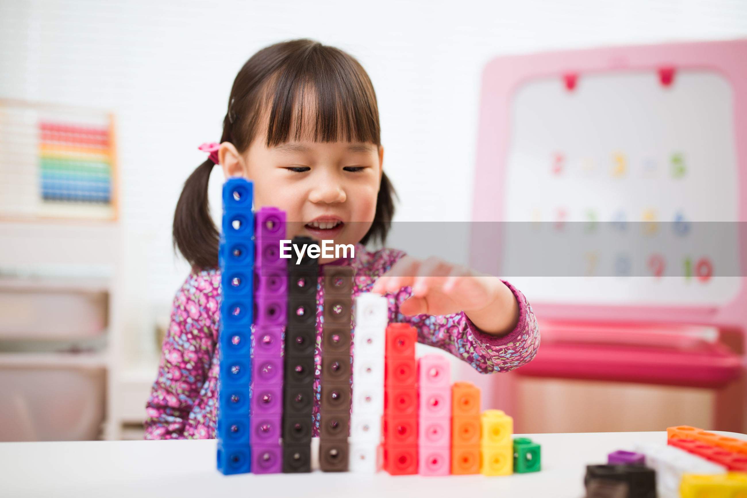 Cute girl stacking toy blocks on table at home