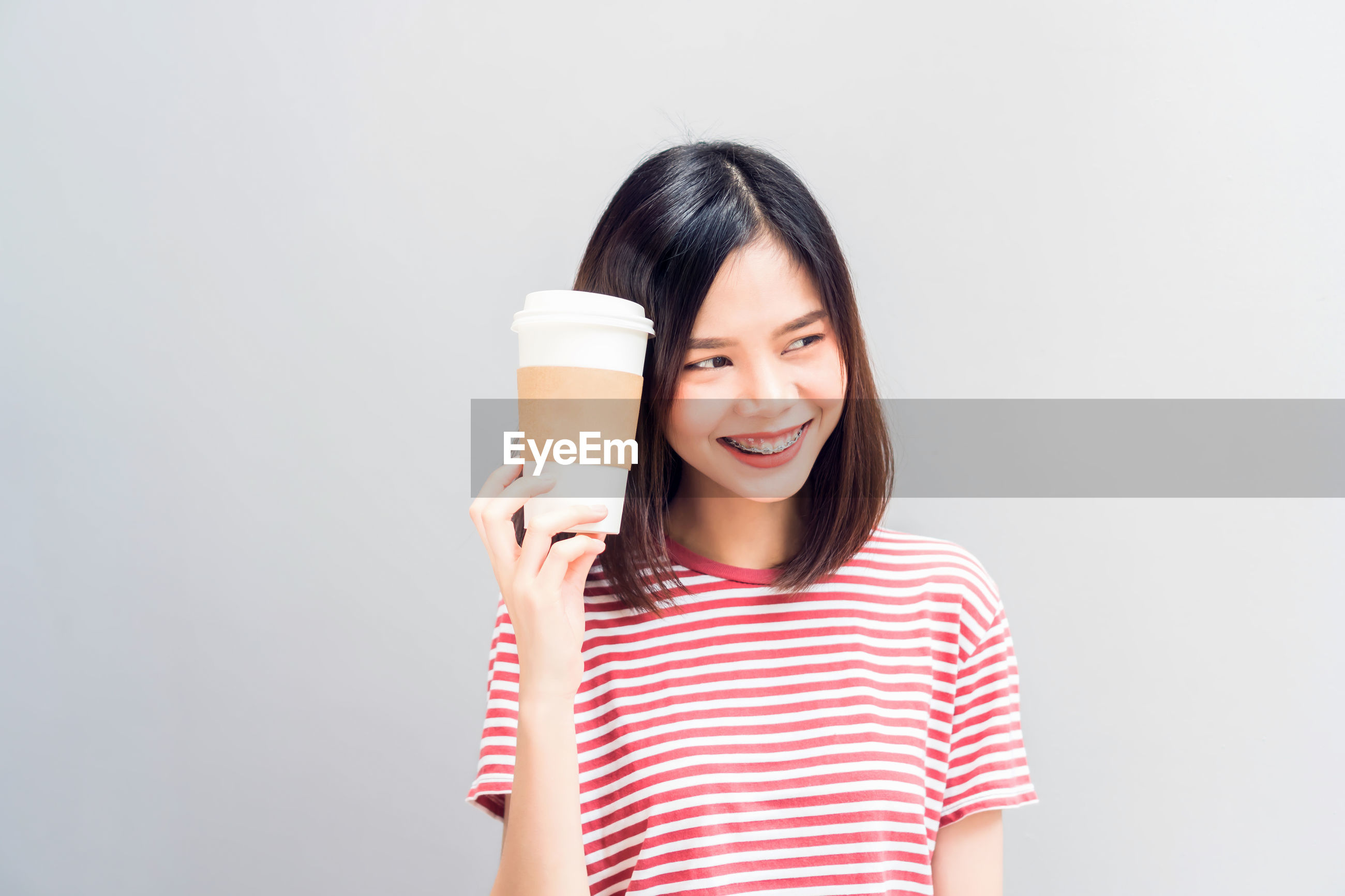 Smiling young woman standing with disposable cup against white background