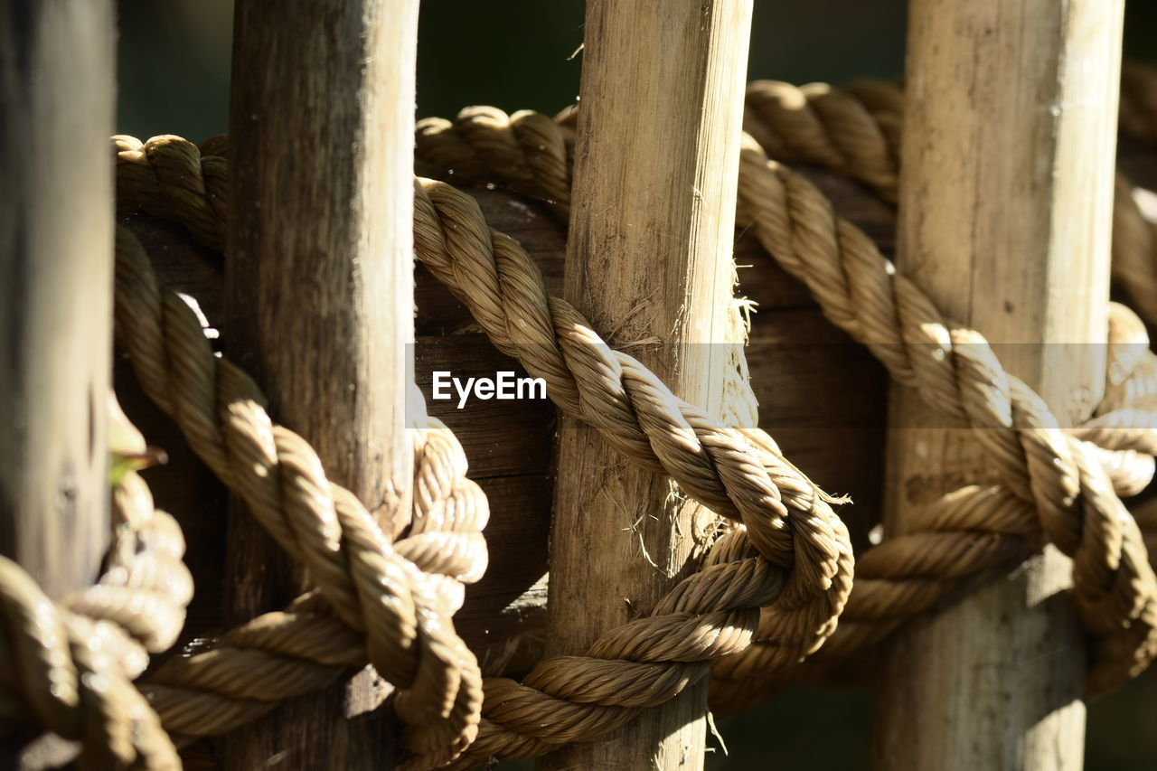 rope, strength, wood - material, no people, close-up, tied up, tied knot, day, pattern, safety, twisted, focus on foreground, security, textured, outdoors, connection, detail, post, brown, wooden post, tangled