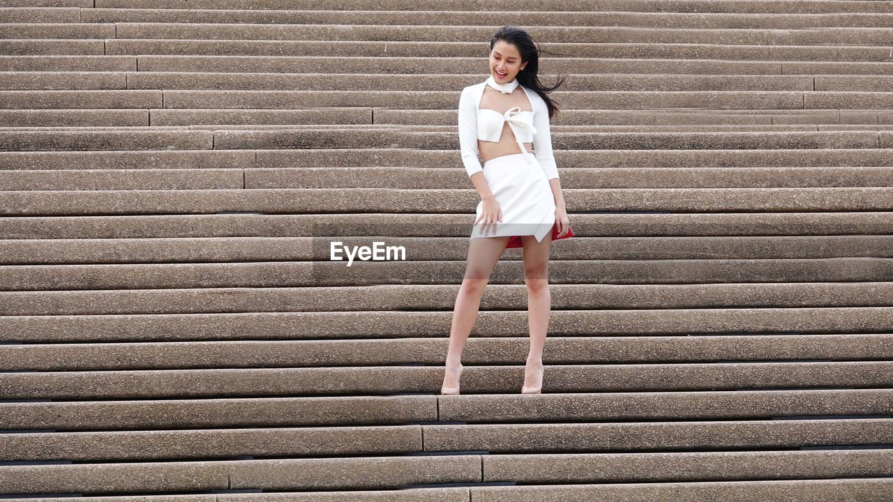 FULL LENGTH PORTRAIT OF YOUNG WOMAN STANDING AGAINST STAIRCASE