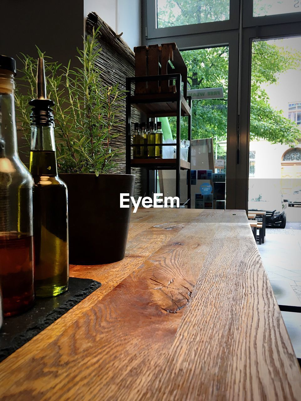 bottle, table, glass - material, container, indoors, food and drink, alcohol, wood - material, drink, refreshment, no people, plant, wine, transparent, glass, window, wine bottle, still life, day, home interior, bar counter
