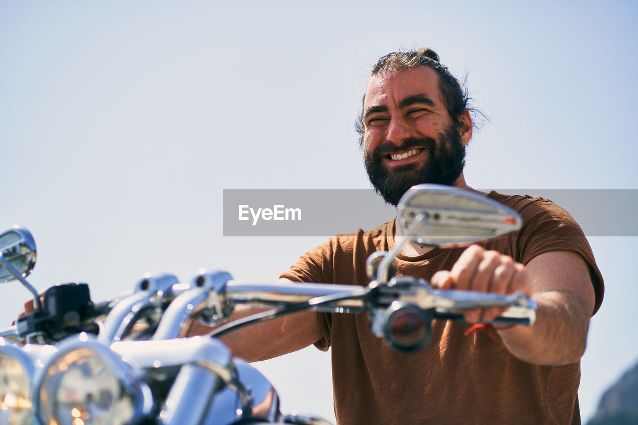 MAN HOLDING BICYCLE AGAINST CLEAR SKY AGAINST CARS