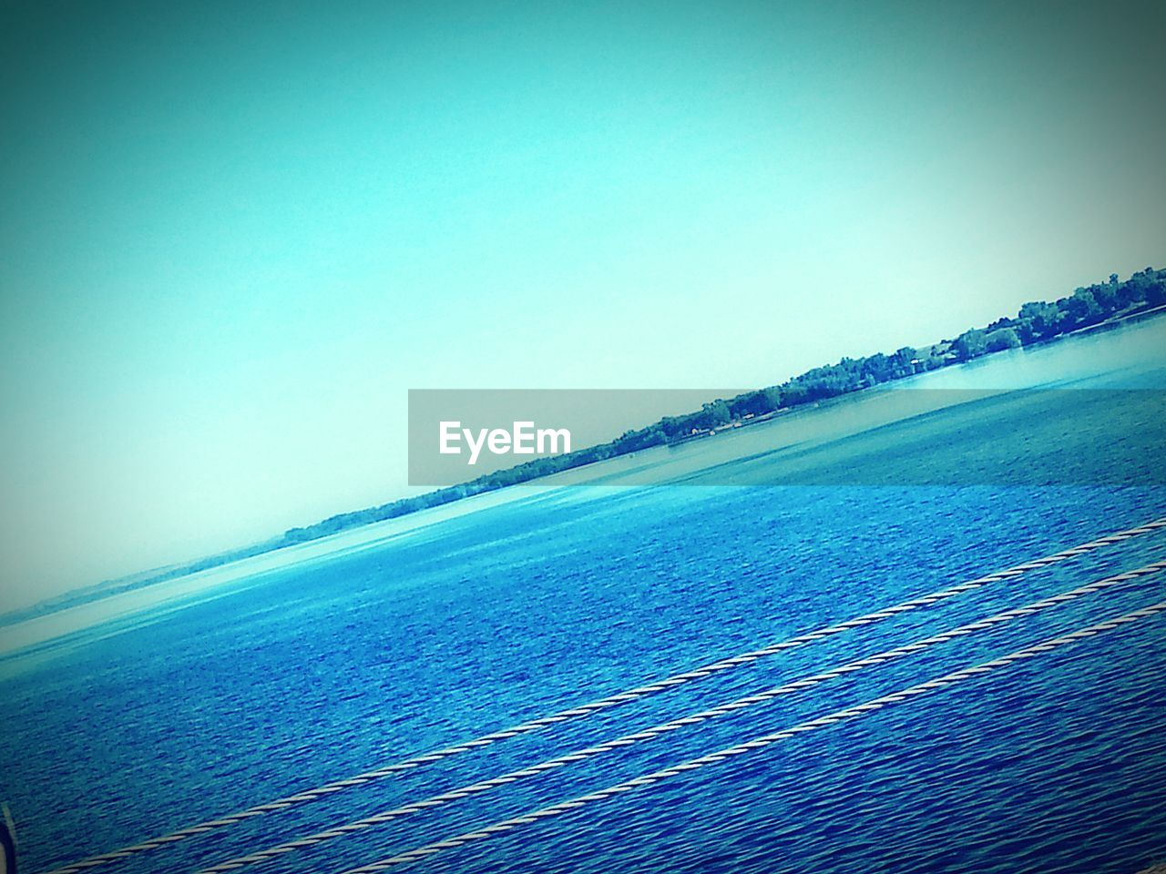 sea, water, clear sky, beauty in nature, scenics, nature, waterfront, horizon over water, rippled, blue, outdoors, tranquil scene, no people, tranquility, day, wake, vacations, sky, wave, nautical vessel