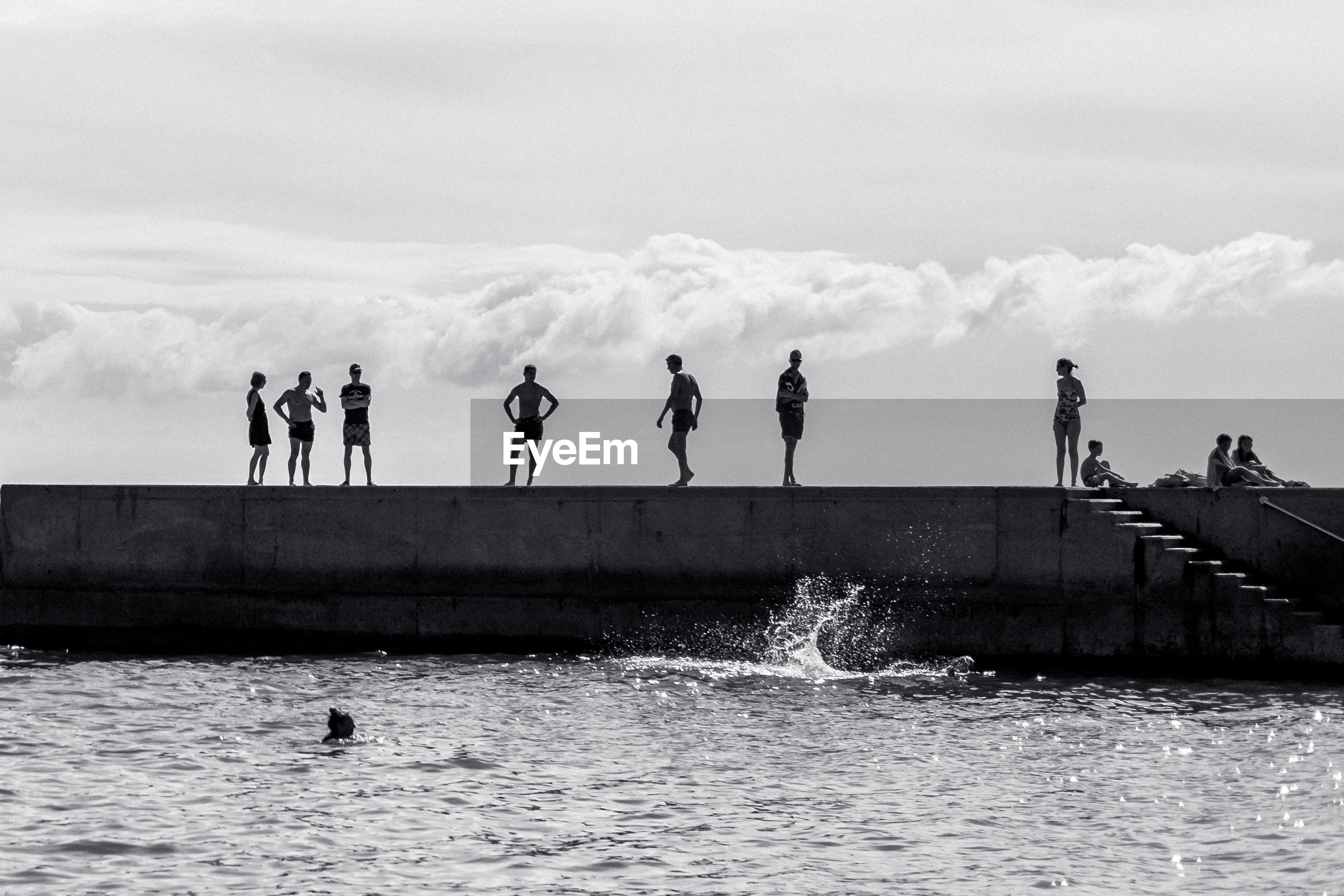 People standing by sea on retaining wall