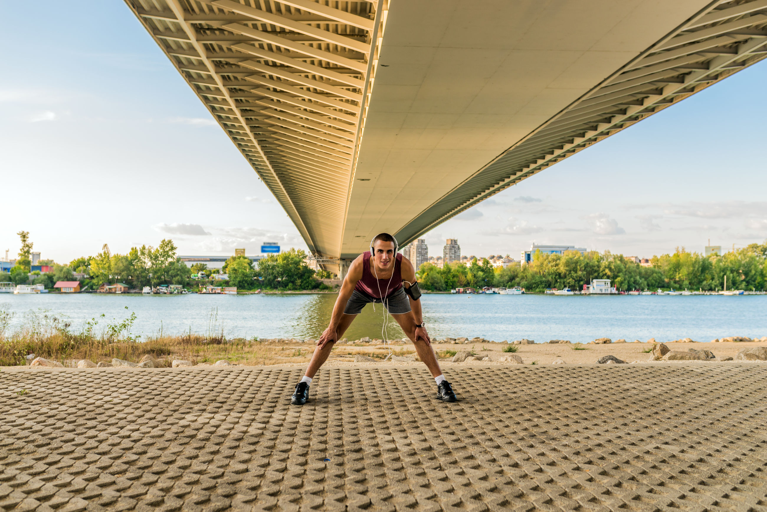 Portrait of handsome man exercising under bridge with river in background