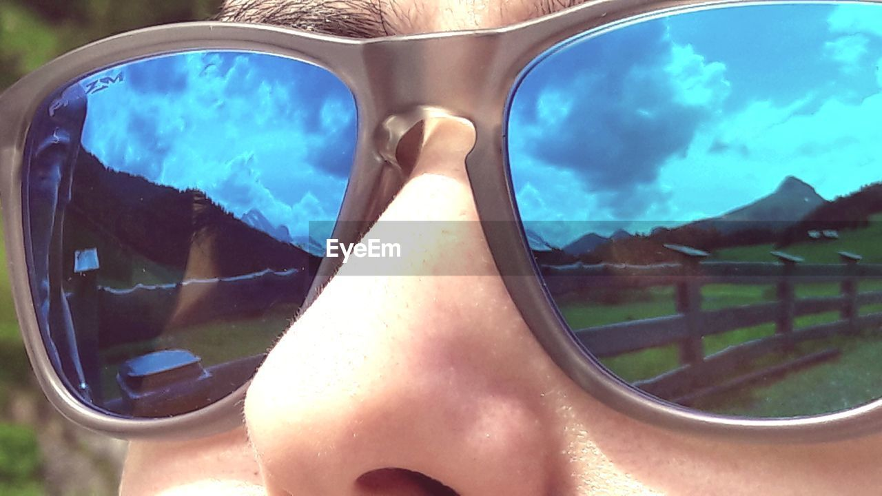 sunglasses, one person, nature, lifestyles, fashion, leisure activity, day, glasses, real people, sunlight, women, reflection, human body part, sky, close-up, outdoors, cloud - sky, summer, adult, body part, swimming pool
