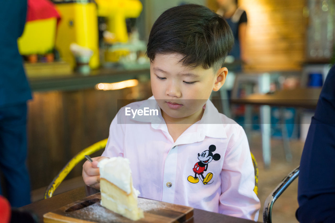 childhood, real people, indoors, child, boys, men, holding, females, males, table, headshot, focus on foreground, looking, food and drink, incidental people, concentration, lifestyles, restaurant, innocence
