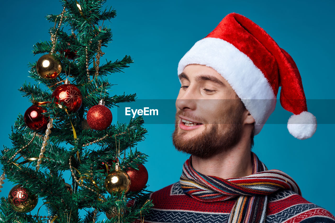 PORTRAIT OF SMILING YOUNG MAN WITH CHRISTMAS TREE AGAINST SKY