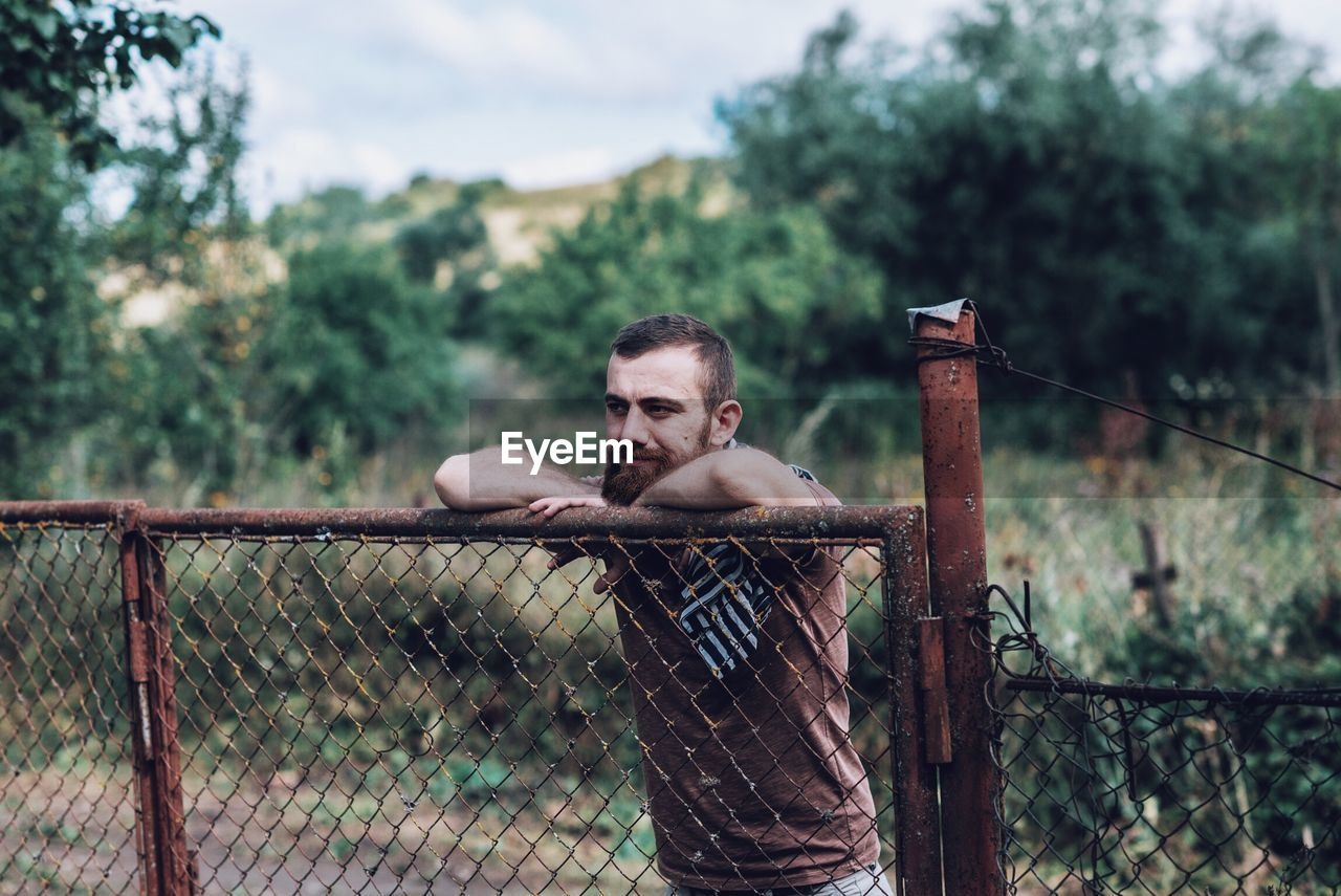 Man Leaning On Rusty Fence