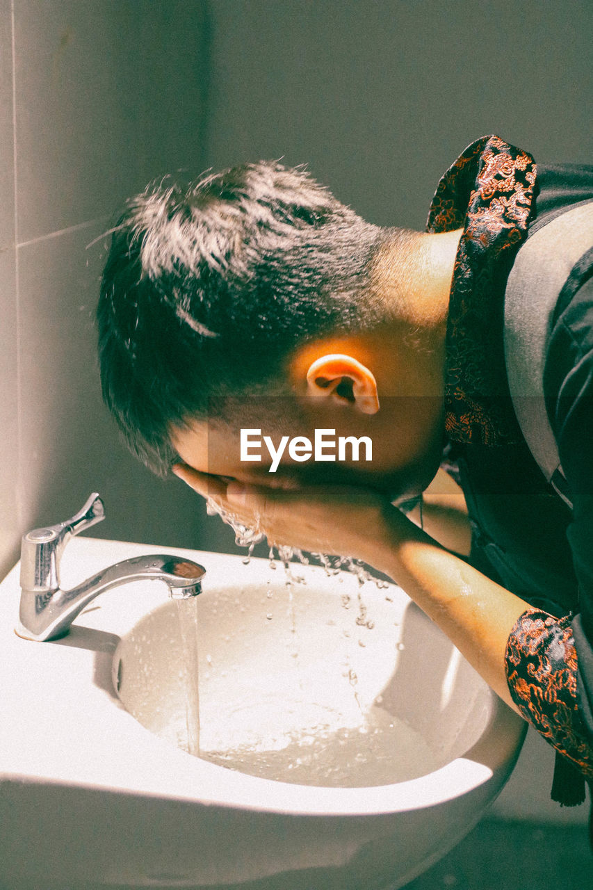 Side View Of Man Washing Face In Bathroom Sink