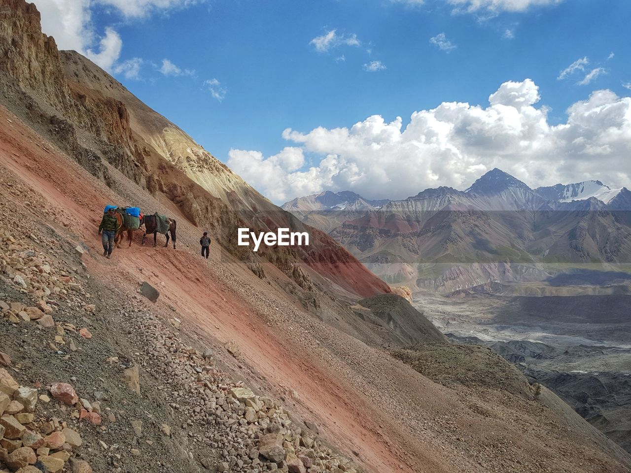 People Walking With Horses Carrying Loads On Mountains Against Sky