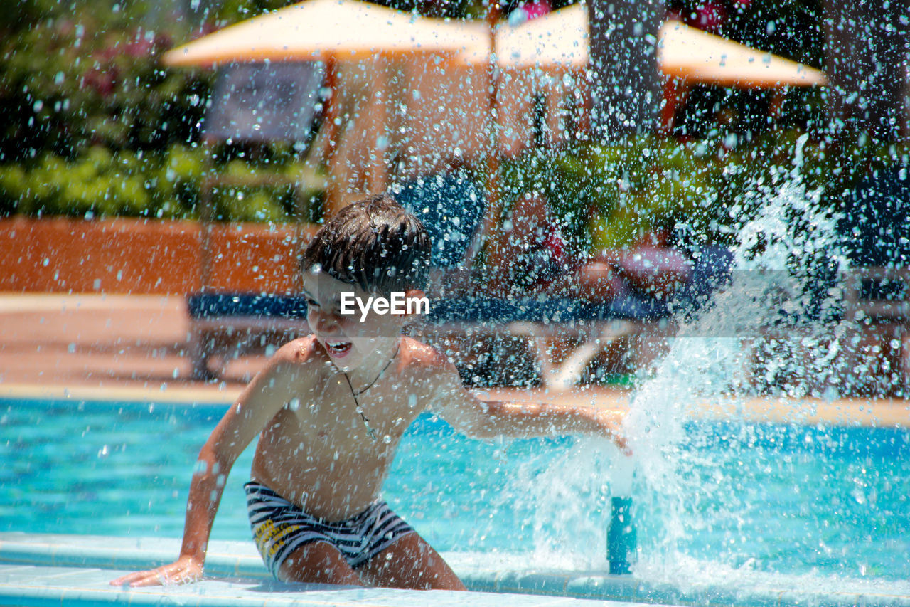 Boy Enjoying By Fountain In Swimming Pool On Sunny Day