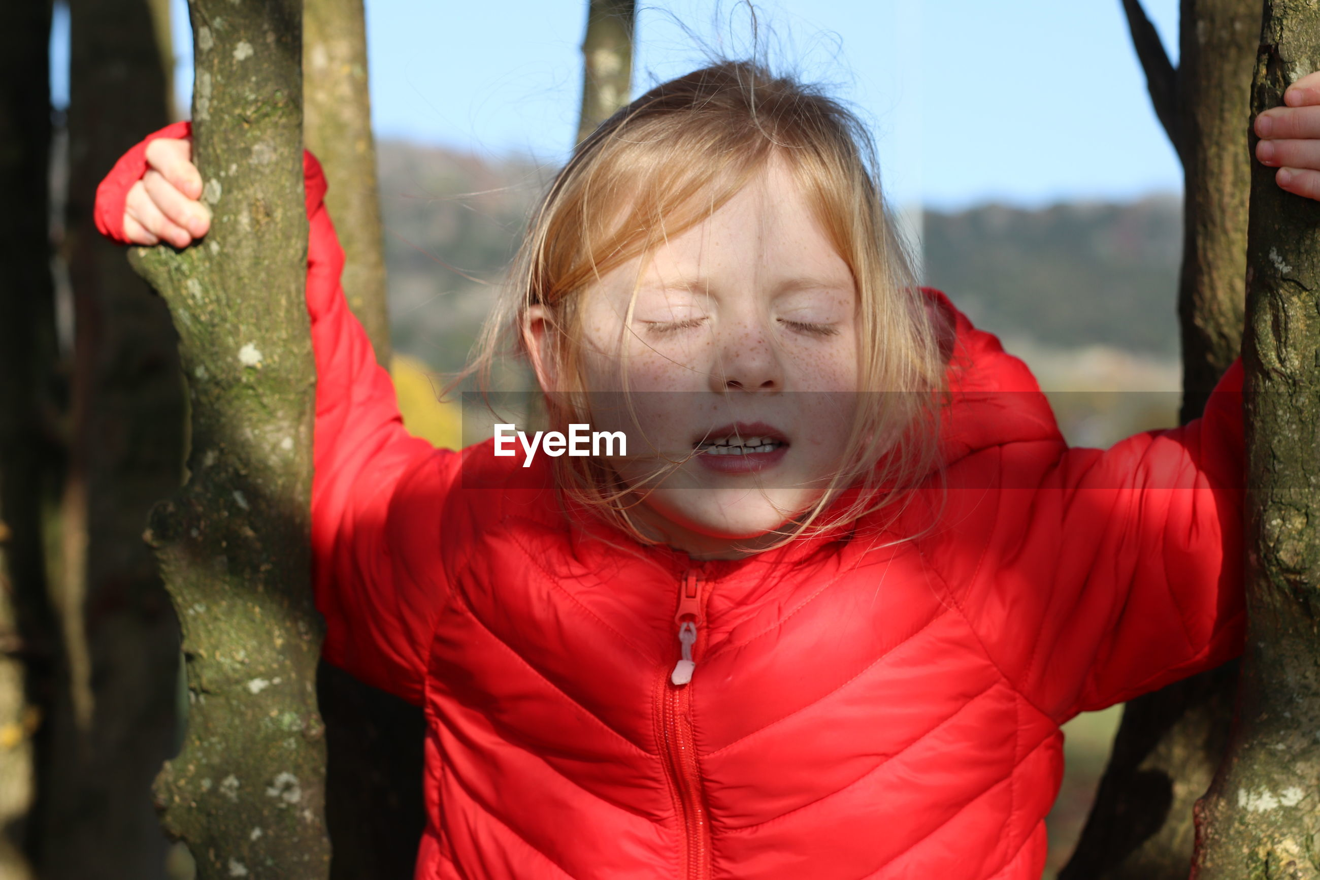 Close-up of girl with closed eyes amidst trees