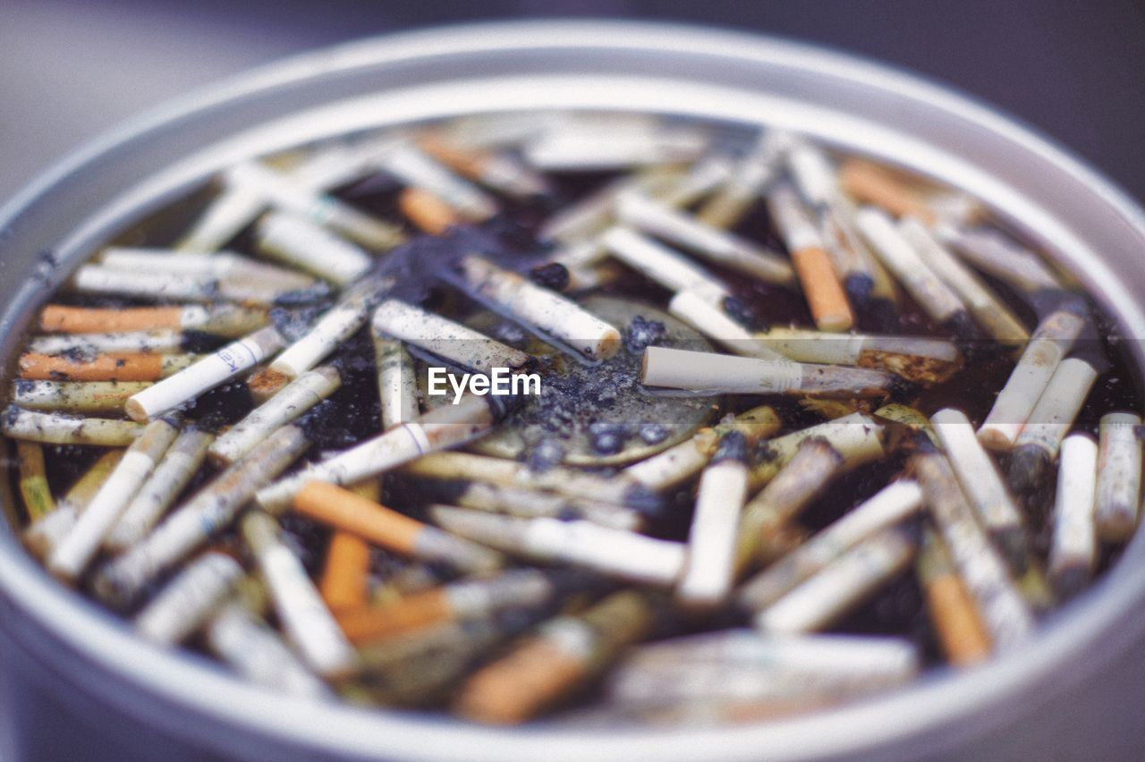 large group of objects, cigarette butt, abundance, close-up, no people, container, bad habit, addiction, indoors, danger, selective focus, ashtray, day