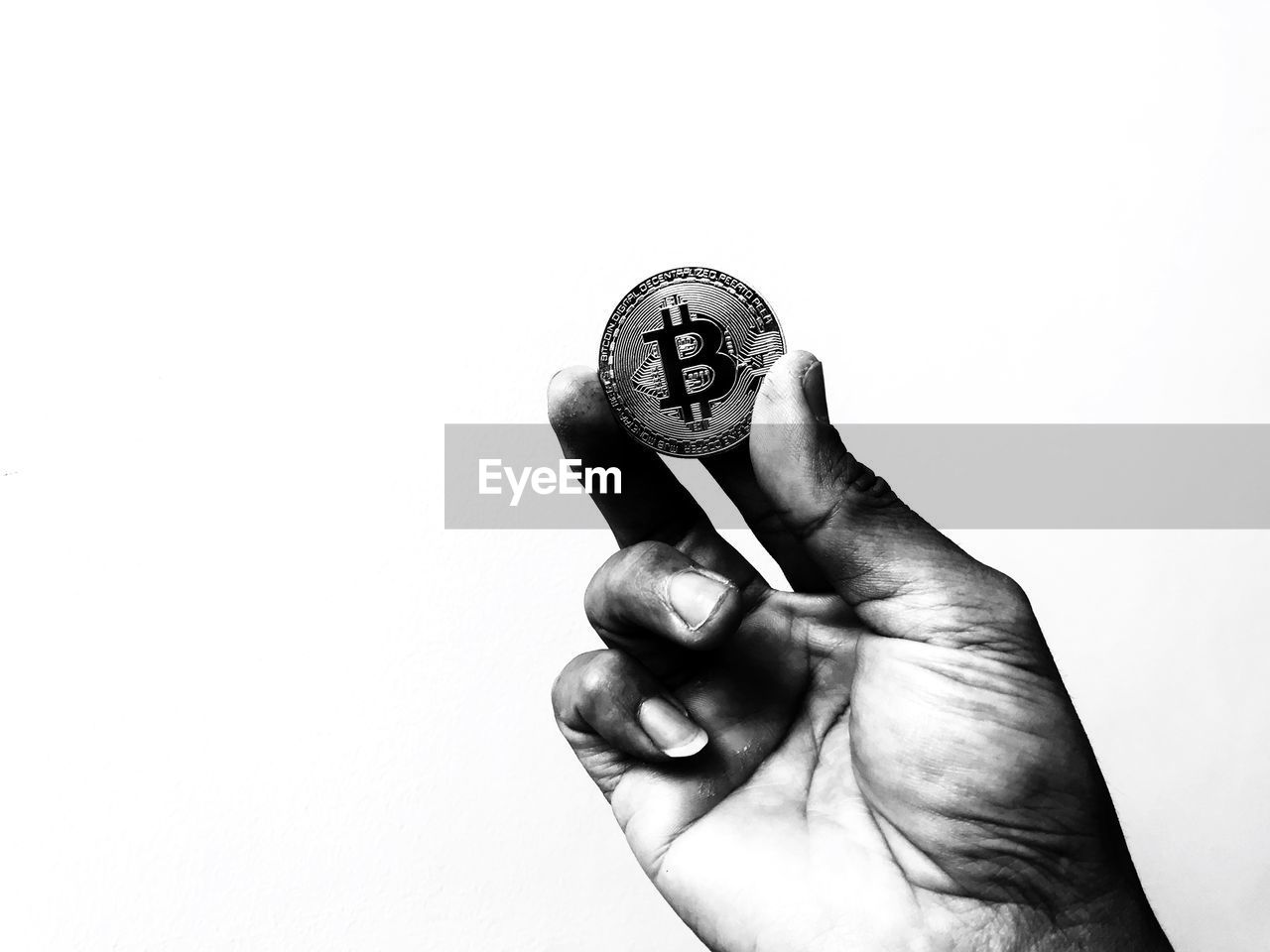 Cropped hand holding bitcoin against white background