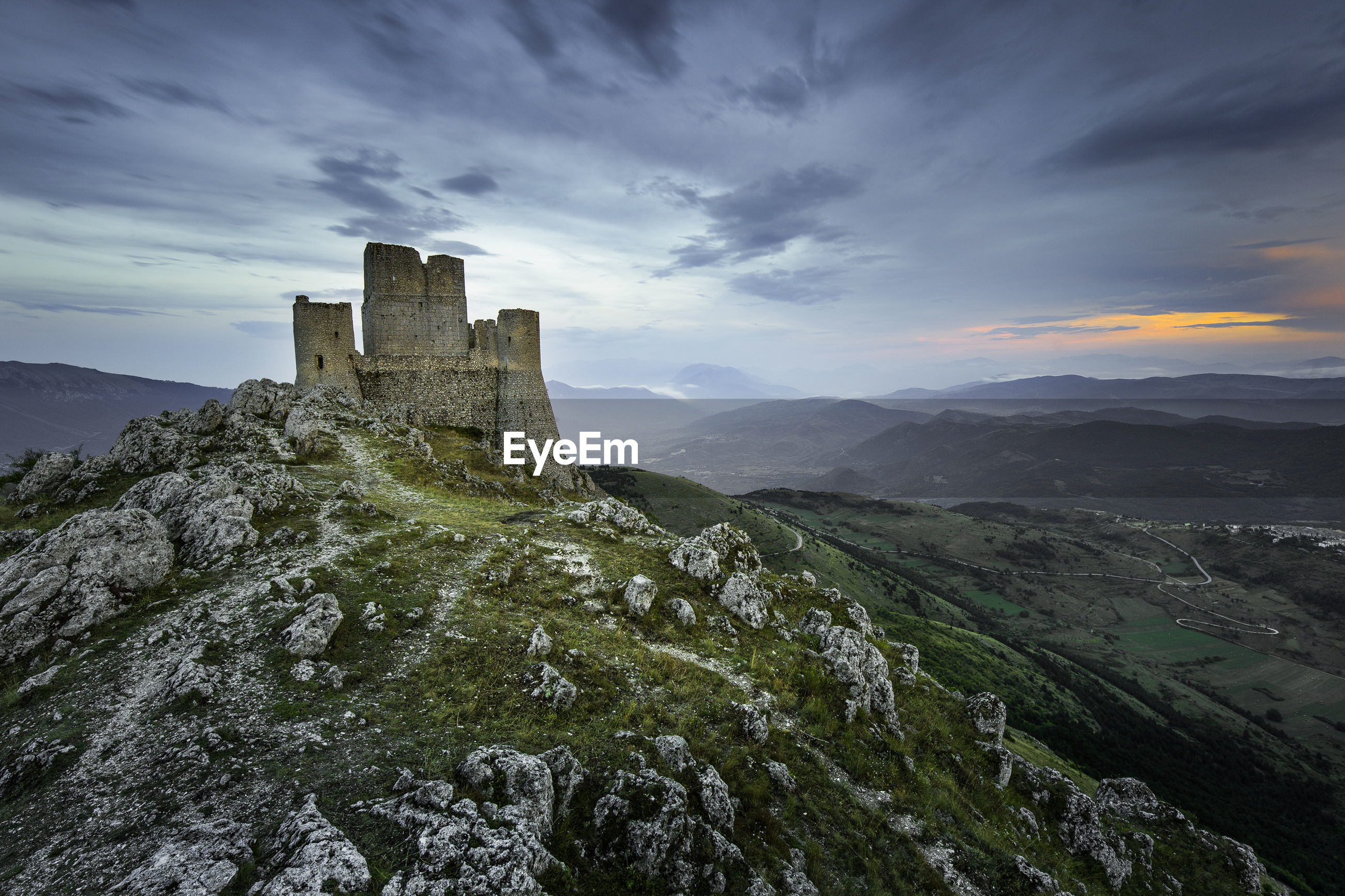 Old ruin on mountain against sky during sunset