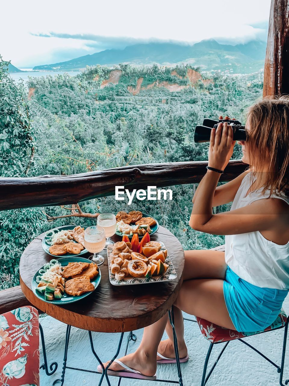 Woman using binoculars while sitting by food on table