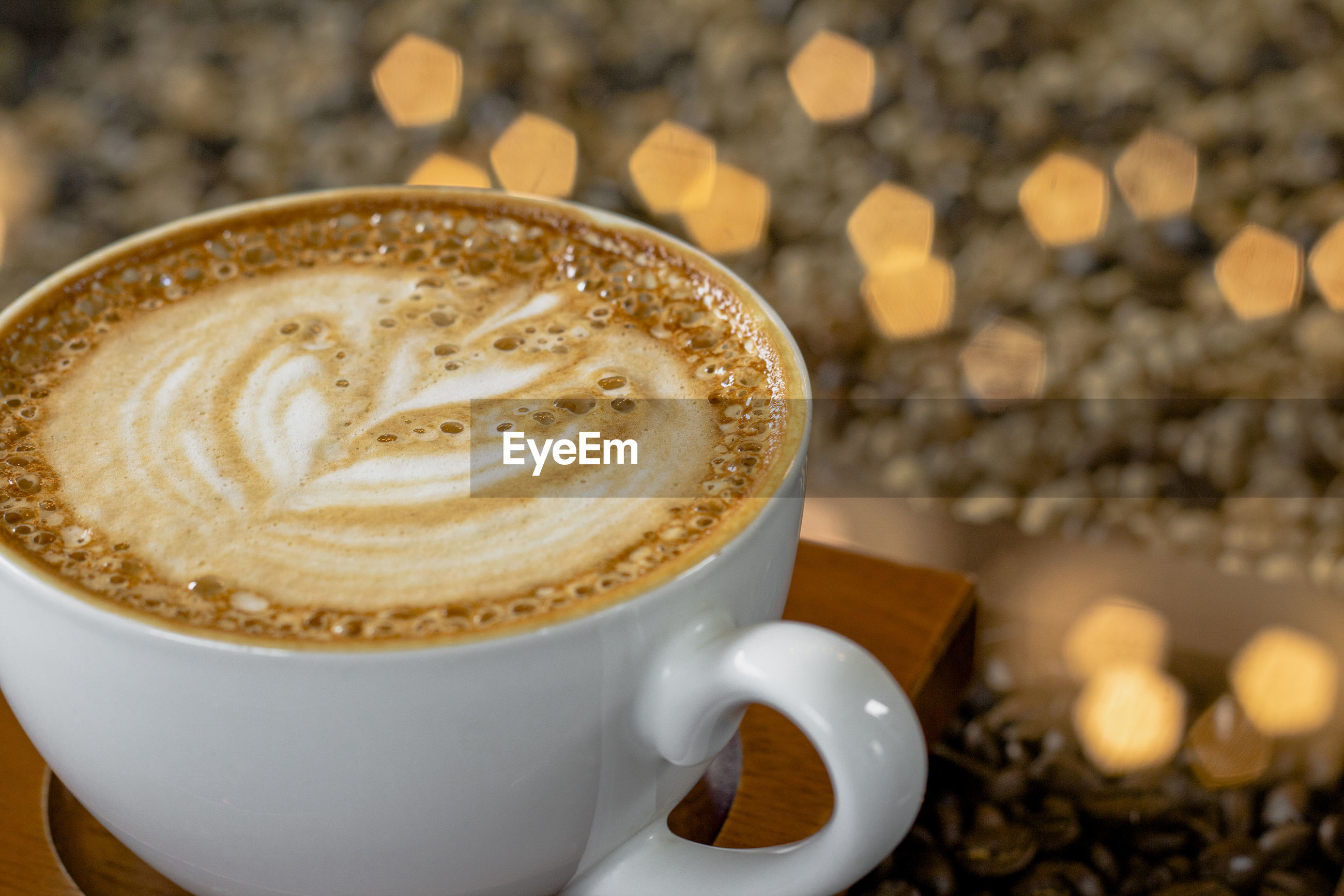 Latte art coffee with bokeh of lights on table, dark tone