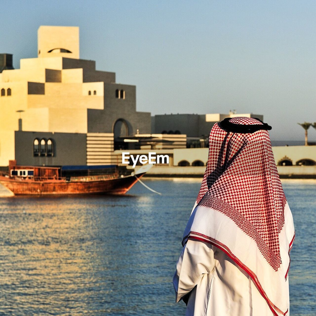 Rear view of an Arabic man looking at moored boat moored in lake against built structure