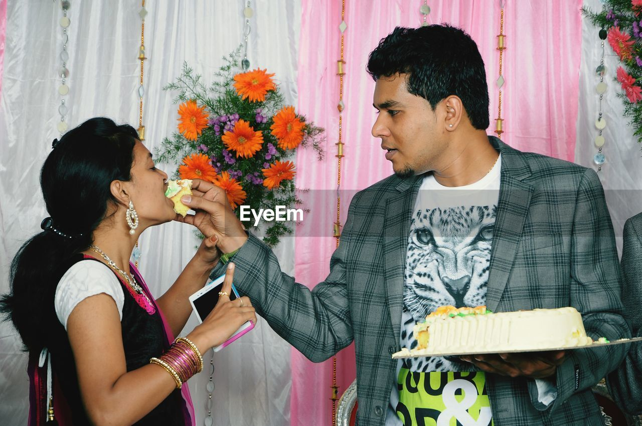 Young Man Feeding Woman During Celebration