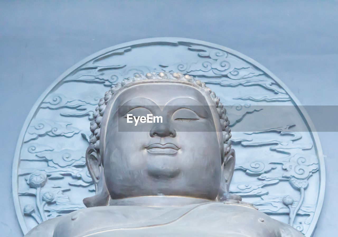 Low angle view of lord buddha statue against sky