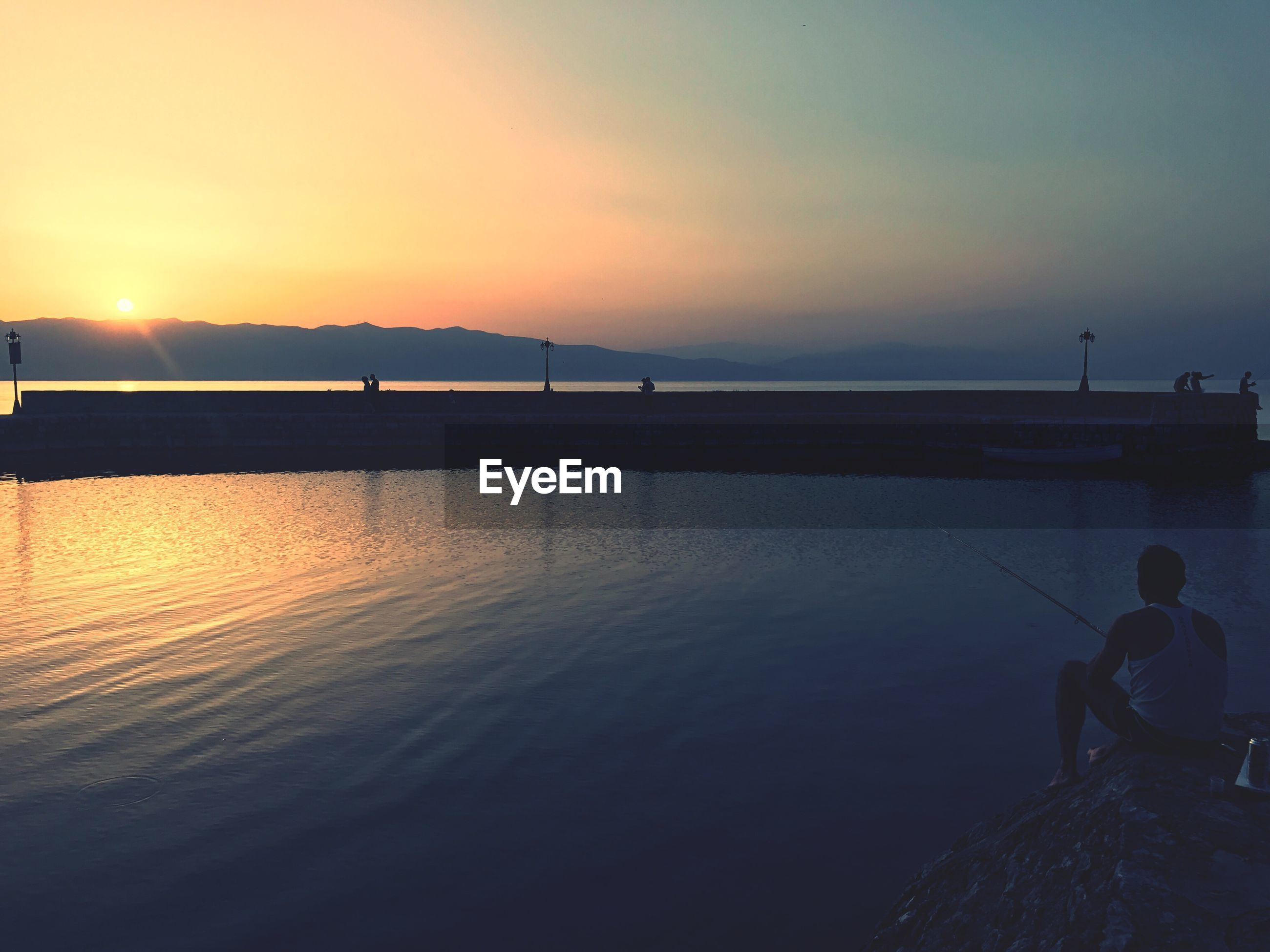 Man fishing by sea during sunset