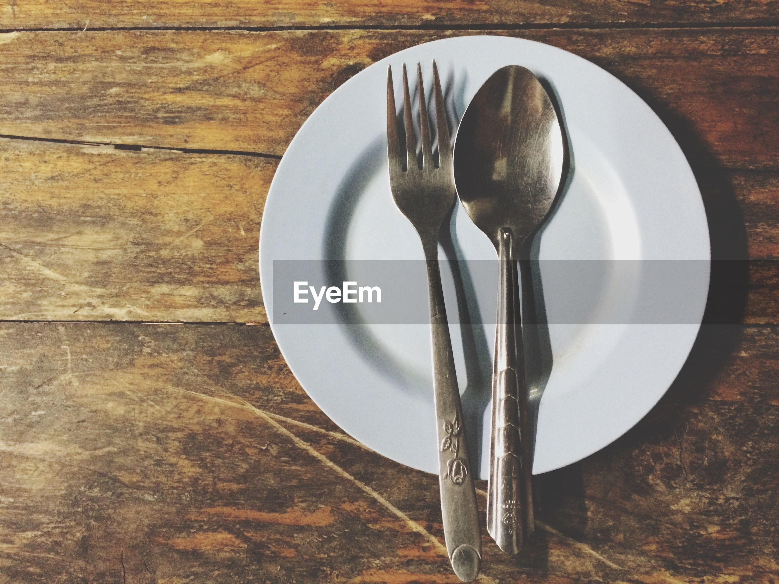 Empty plate with spoon and fork on table