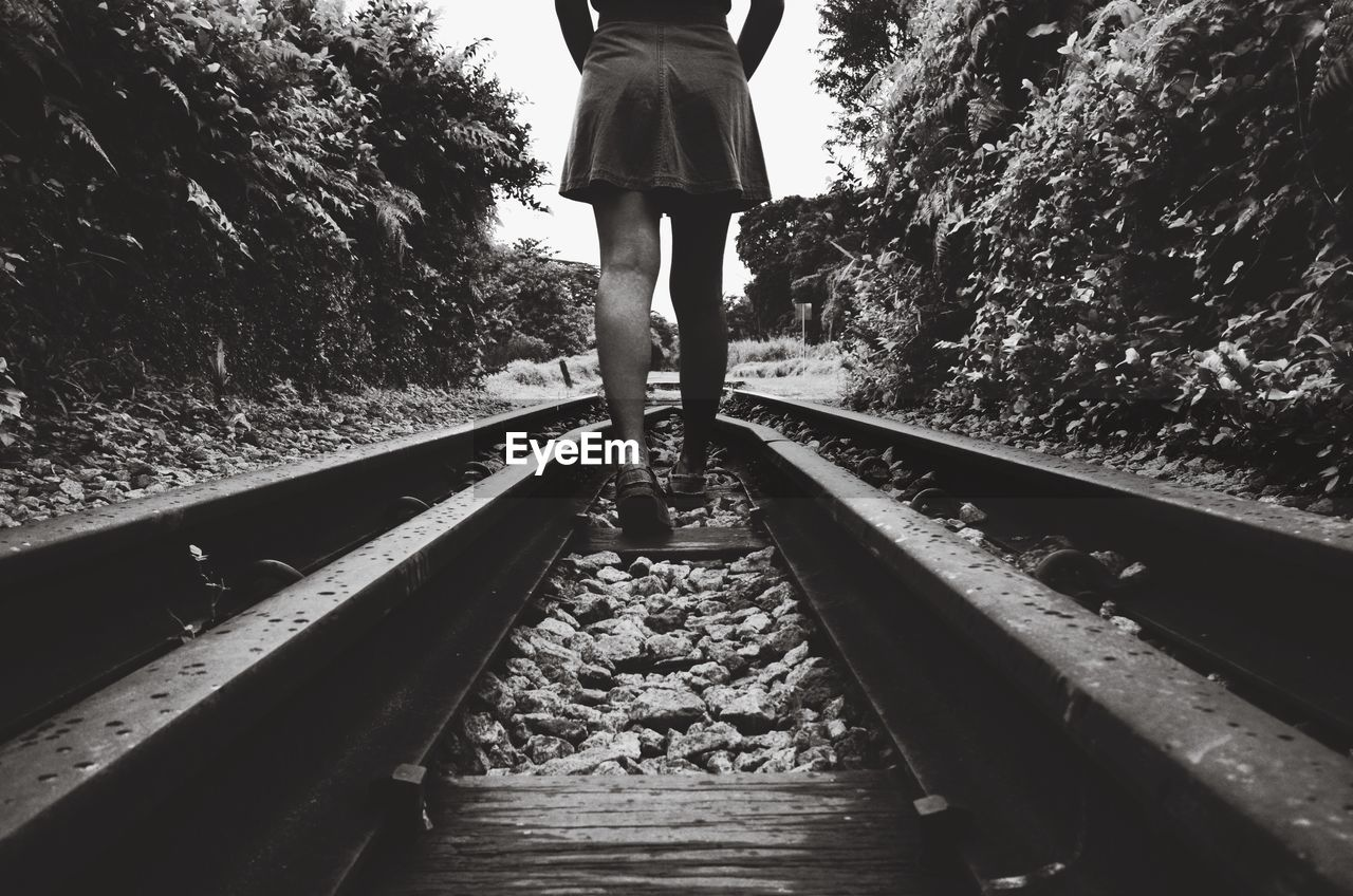 Low Section Of Woman Walking On Railroad Tracks