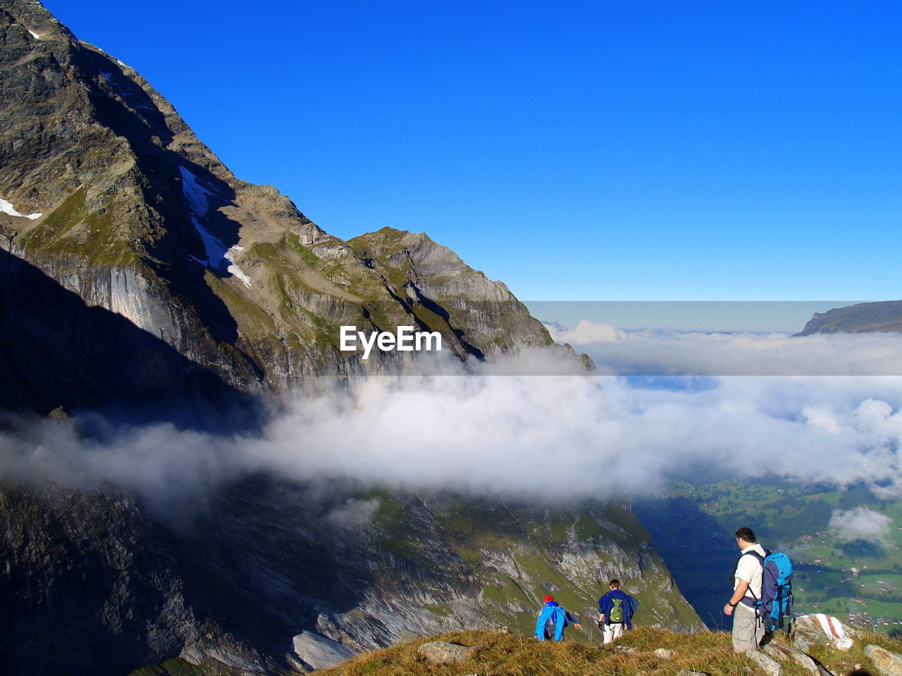 High angle view of friends walking on mountain against blue sky