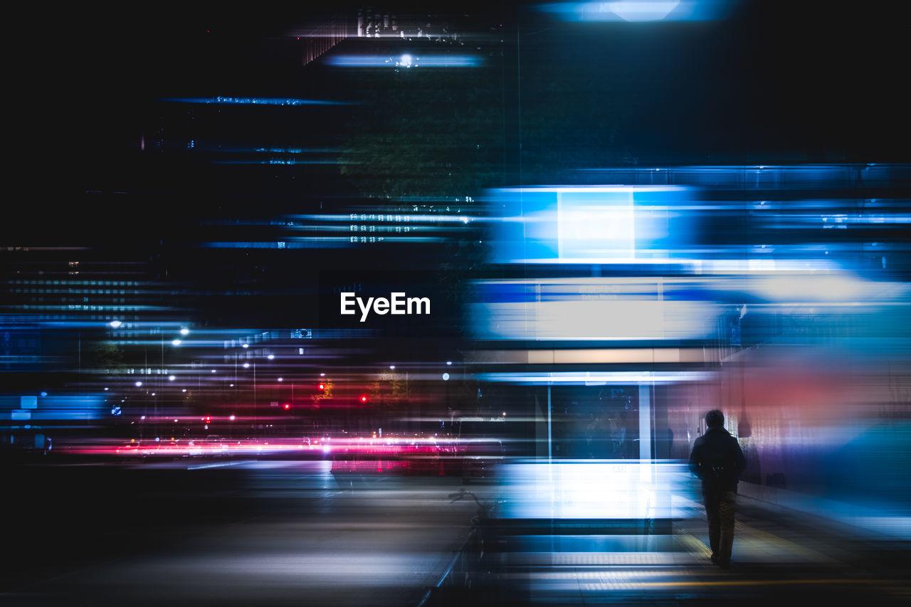 Rear View Of Man In Illuminated City At Night