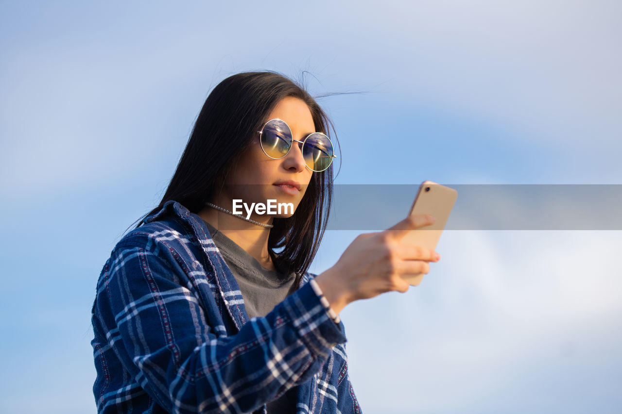 one person, sunglasses, glasses, fashion, young adult, wireless technology, young women, lifestyles, mobile phone, technology, communication, smart phone, leisure activity, real people, using phone, sky, portrait, telephone, holding, hair, hairstyle, beautiful woman, outdoors
