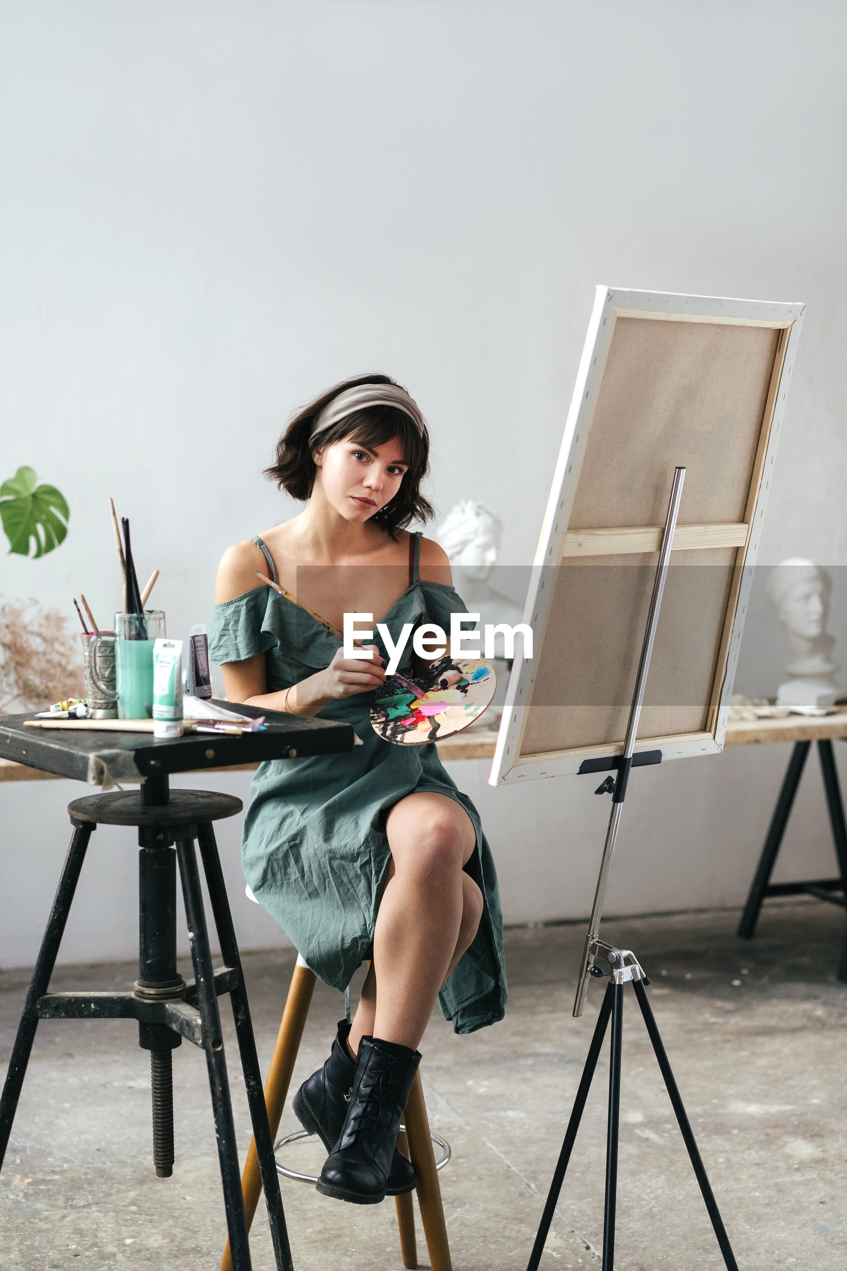 Portrait of young woman painting on canvas while sitting on table