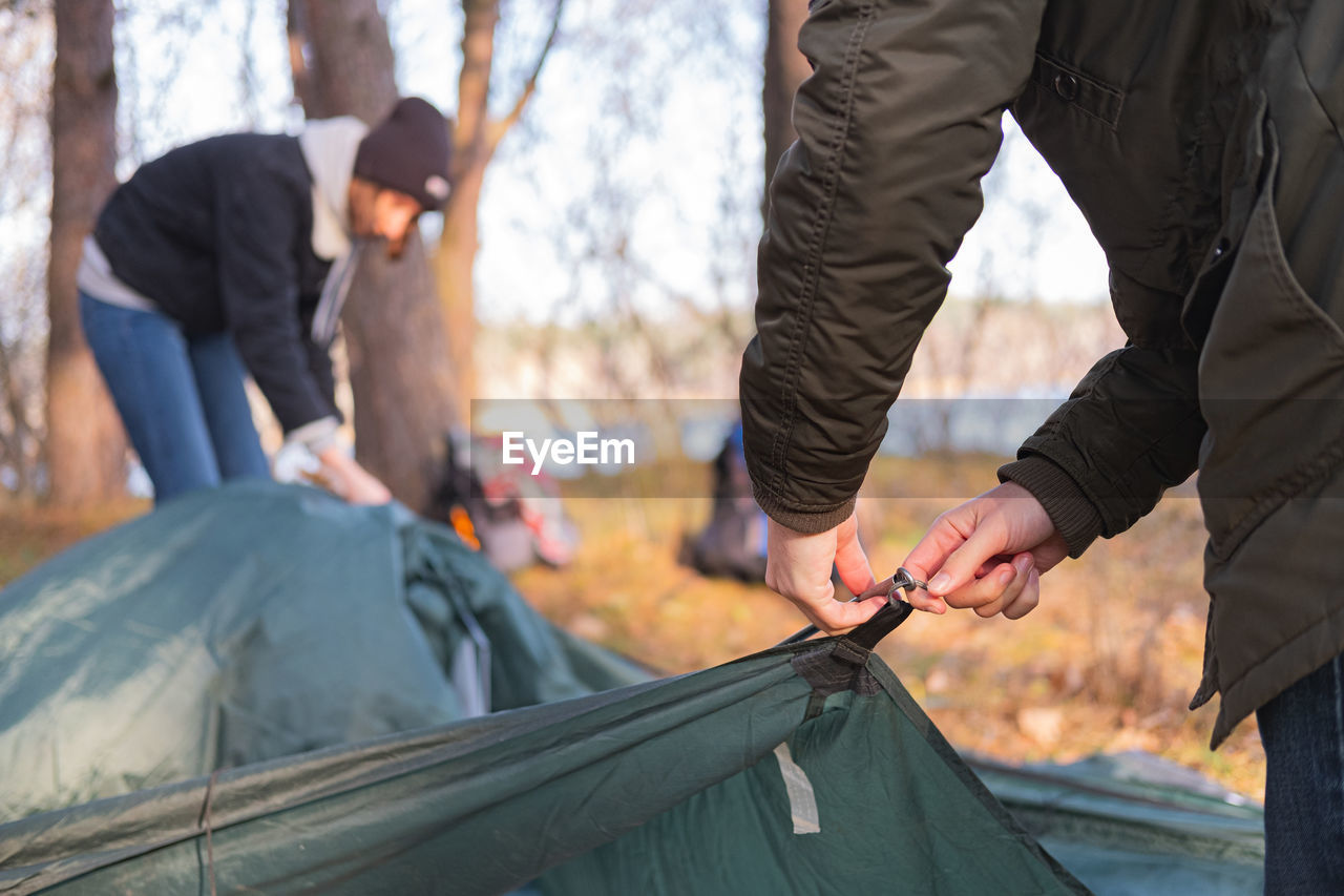 Couple making tent at campsite