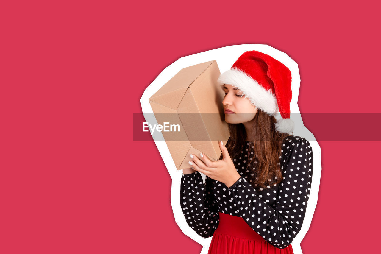 Young woman holding gift box against red background