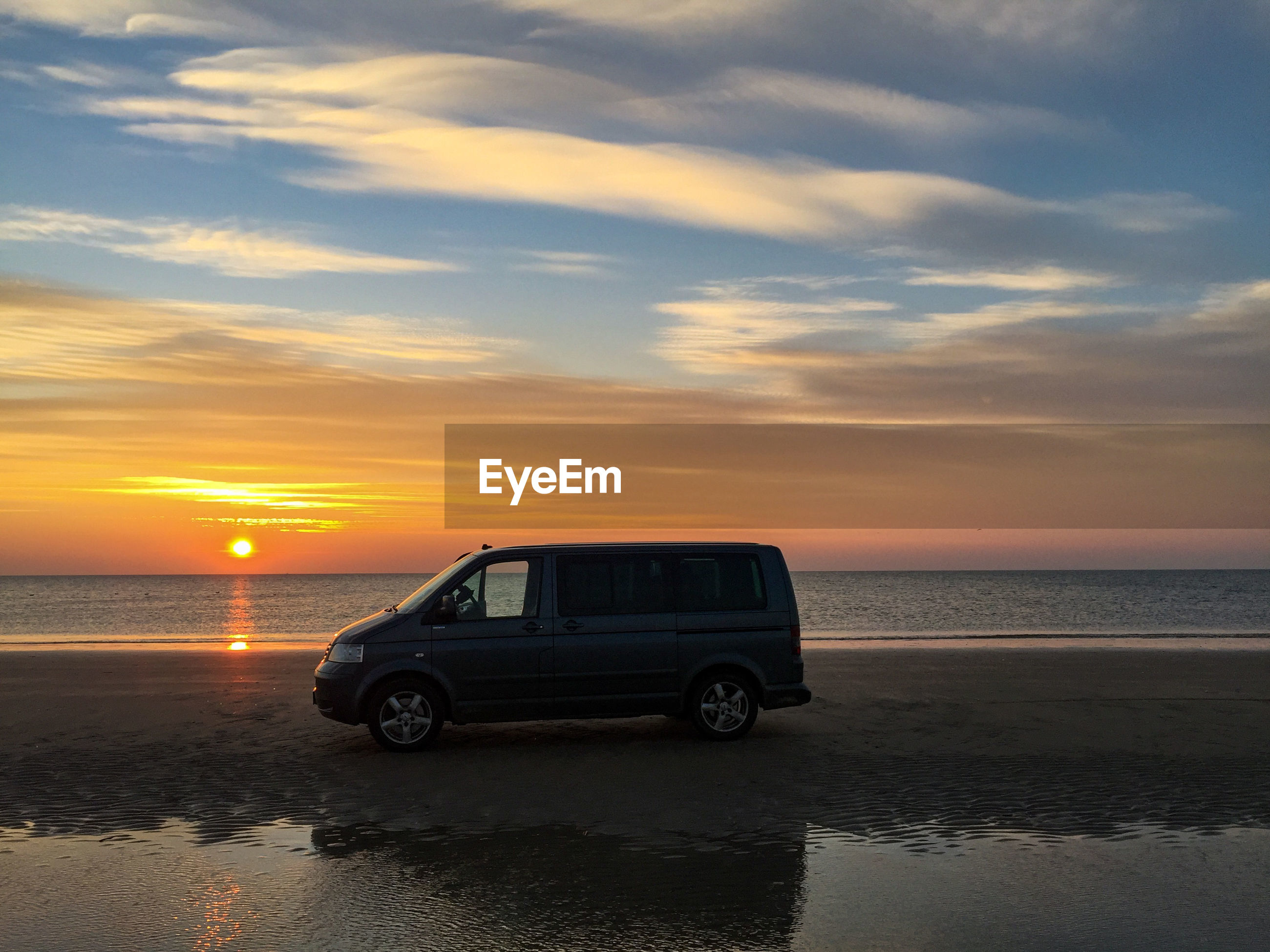 CAR ON SEA SHORE AGAINST SKY DURING SUNSET